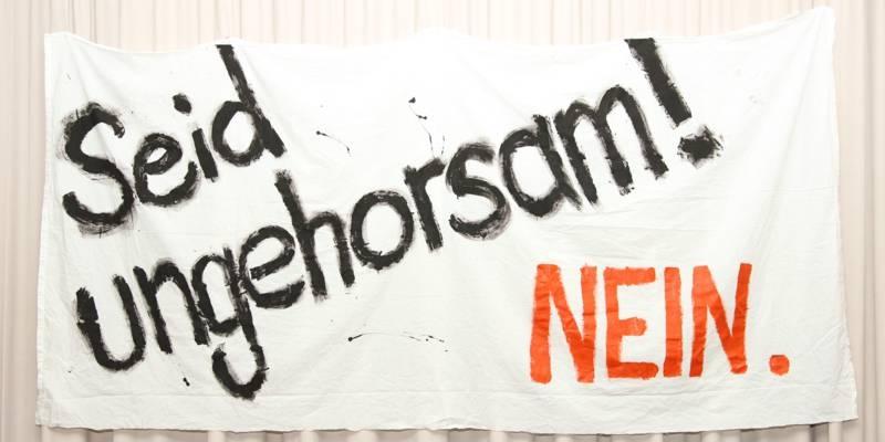 """Banner mit der Aufschrift """"Seid ungehorsam! Nein."""""""
