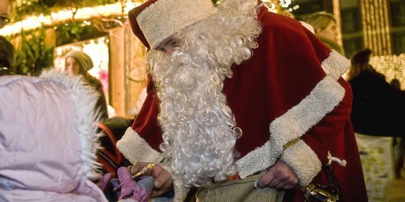 Der Weihnachtsmann überreicht einem Kind ein kleines Geschenk