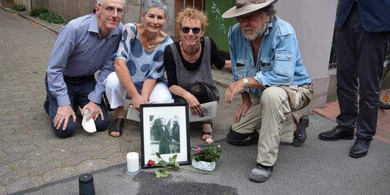 Künstler Gunter Demnig (rechts) bei der Stolpersteinverlegung für Gutta Meyer. Neben ihm Margaret Jacobs, die Urenkelin von Gutta Meyer, zusammen mit ihrer Lebensgefährtin Jules Rolfe und ihrem Bruder John Jacobs.