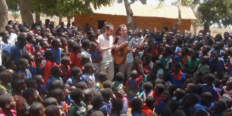 Zwei Musiker treten zwischen Schülerinnen und Schülern aus Malawi unter freiem Himmel auf