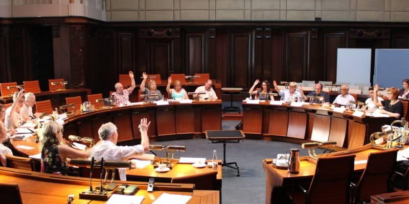 Etwa 20 Personen sitzen kreisförmig hinter Pulten im Hodlersaal im Neuen Rathaus. Die elf stimmberechtigten Mitglieder heben die Hand zur Abstimmung.