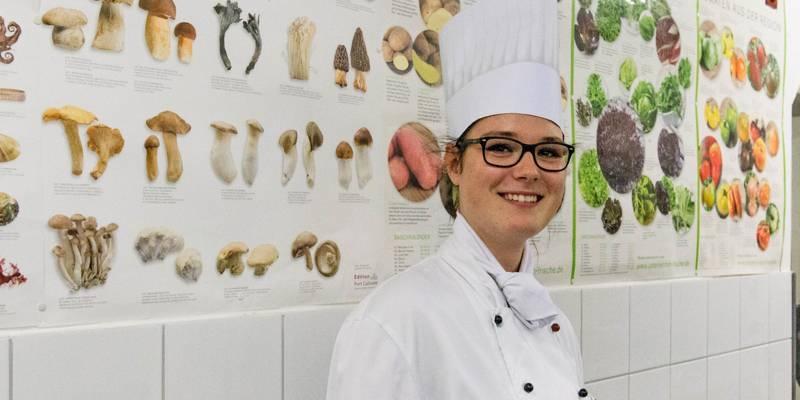 Eine junge Frau in weißer Koch-Berufsbekleidung und Mütze steht vor einer gefliesten Wand, die durch Poster von Pilzen und Gemüsesorten aufgelockert wird.