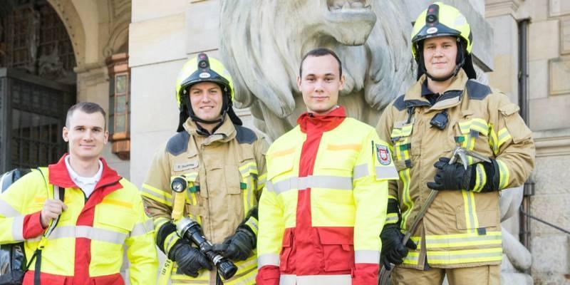 Zwei Auszubildende zum Notfallsanitäter und zwei Auszubildende für den Feuerwehrtechnischen Dienst mit ihrer Arbeitsausrüstung