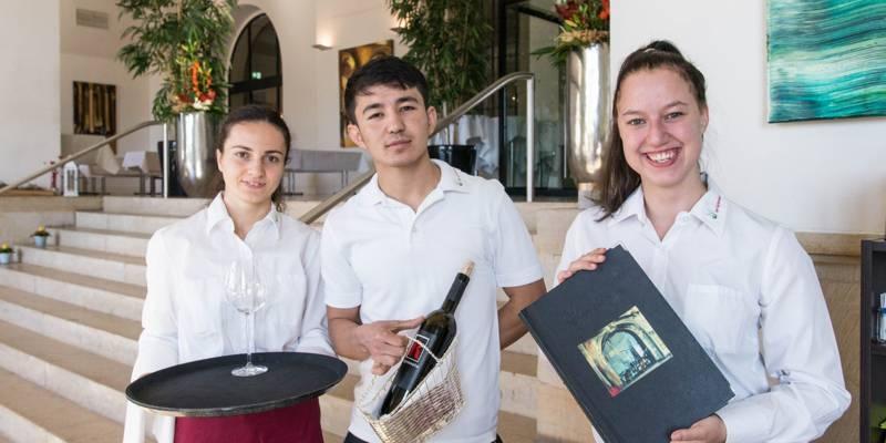 Zwei junge Frauen und ein Mann in Berufskleidung im Restaurant Gartensaal mit Tablett, Weinflasche und Speisekarte