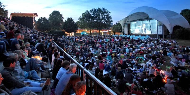 Menschen auf einer Tribüne und auf einer Rasenfläche vor einer Open-Air-Kino-Leinnwand.