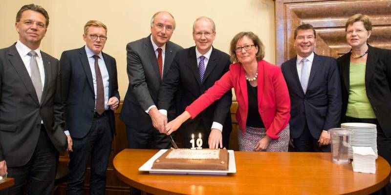 Zwei Frauen und fünf Männer schneiden eine Torte an.