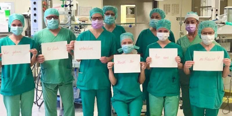 """Medizinisches Personal mit Mundschutz, alle halten Kärtchen hoch deren Aufschriften zusammen den Satz """"Wir gehen für Euch arbeiten bleibt Ihr für uns zu Hause"""" ergeben."""