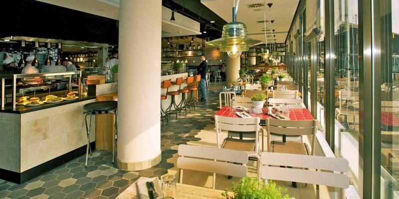 Tische mit Stühlen an einer Glasfront in einem Restaurant.