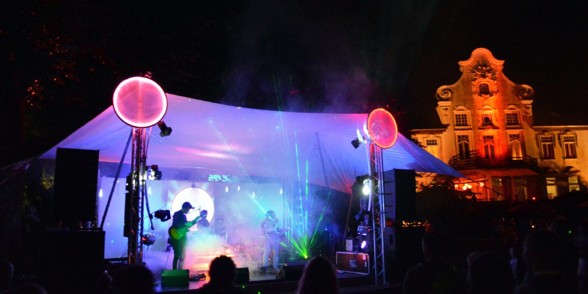 Eine Band spiel auf einer Bühne, im Hintergrund ist das KulturGut Poggenhagen.