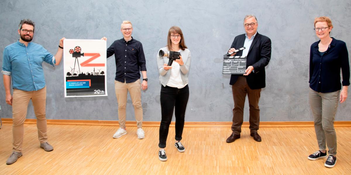 Drei Männer und zwei Frauen stehen nebeneinander in einem Veranstaltungsraum. Die Männer links halten gemeinsam ein Plakat. Daneben, in der Mitte, hält eine Frau eine Filmkamera. Der Mann neben ihr, auf der anderen Seite, hält eine Filmklappe.