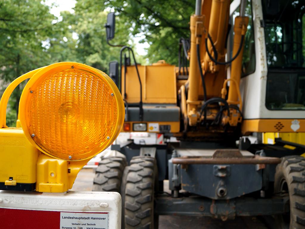 Im Vordergrund eine Baustellenlampe, im Hintergrund ein Bagger