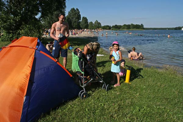 Strandmuschel, Familie mit Kind und Kinderkarre am Altwarmbüchener See, im Hintergrund badende Menschen
