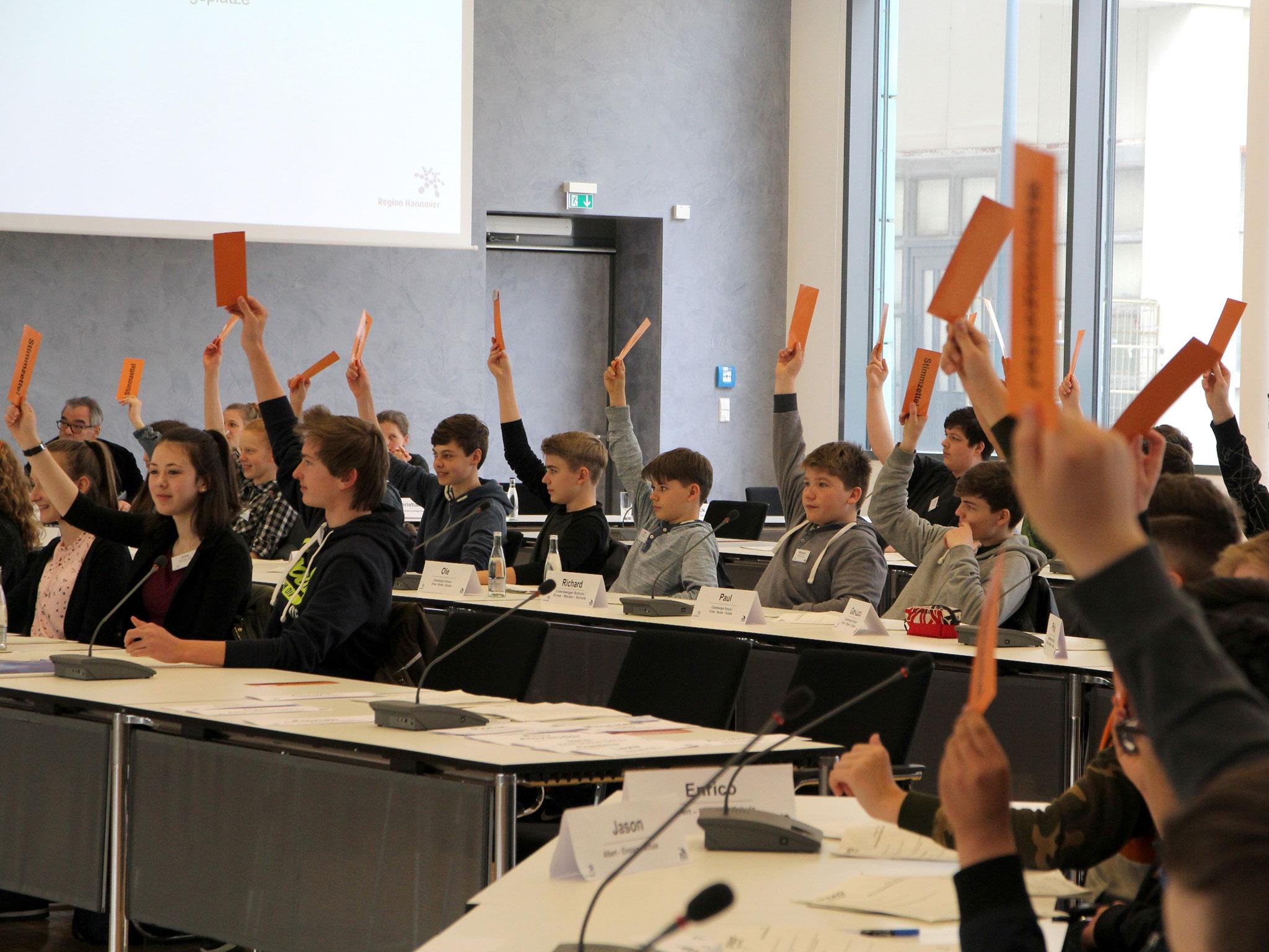 Mehrere Schülerinnen und Schüler sitzen an Tischreihen. Sie halten Kärtchen in die Höhe zum Zweck einer Abstimmung.