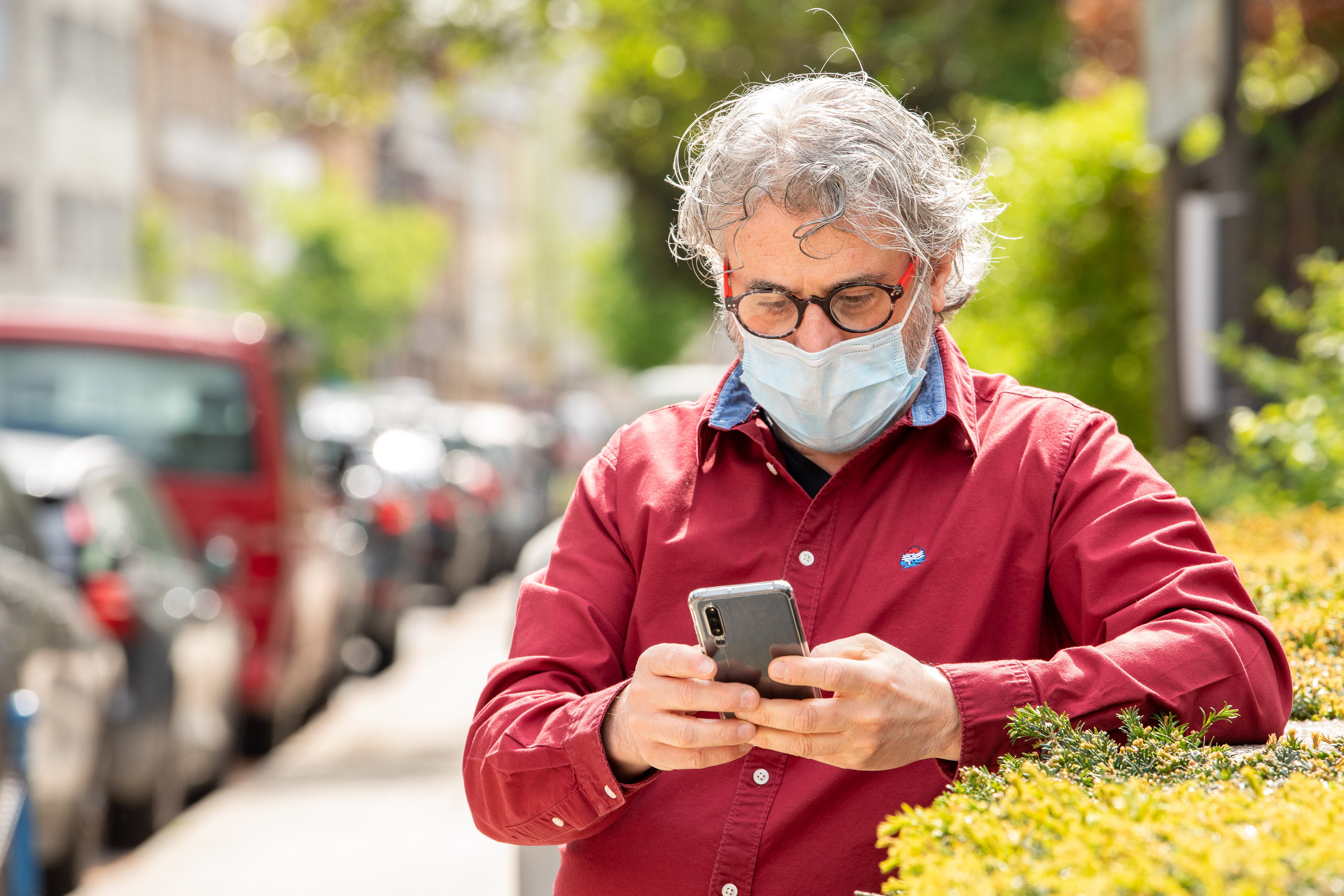 A man with a face mask using an application on his smartphone