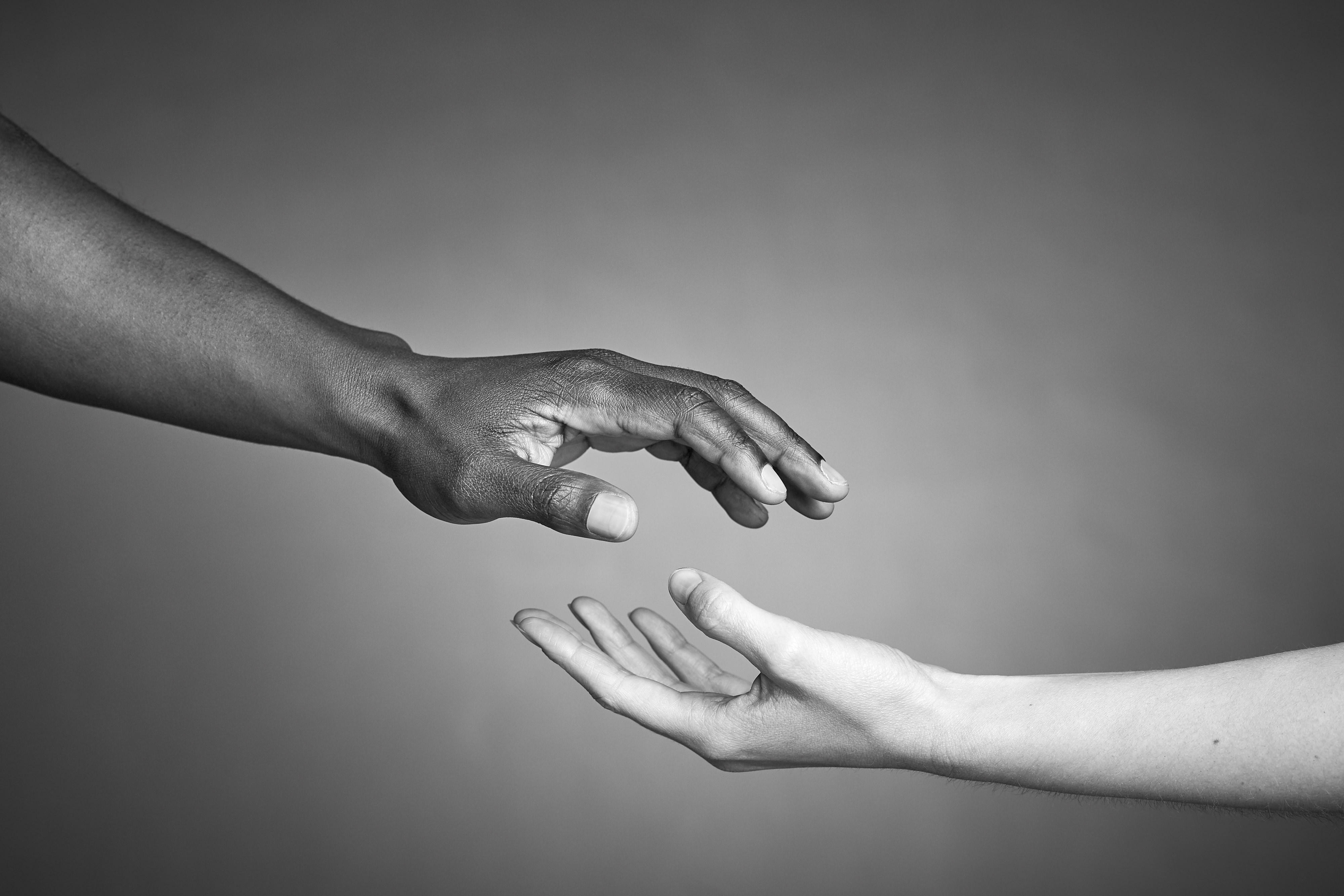 Black and white hands together against racism