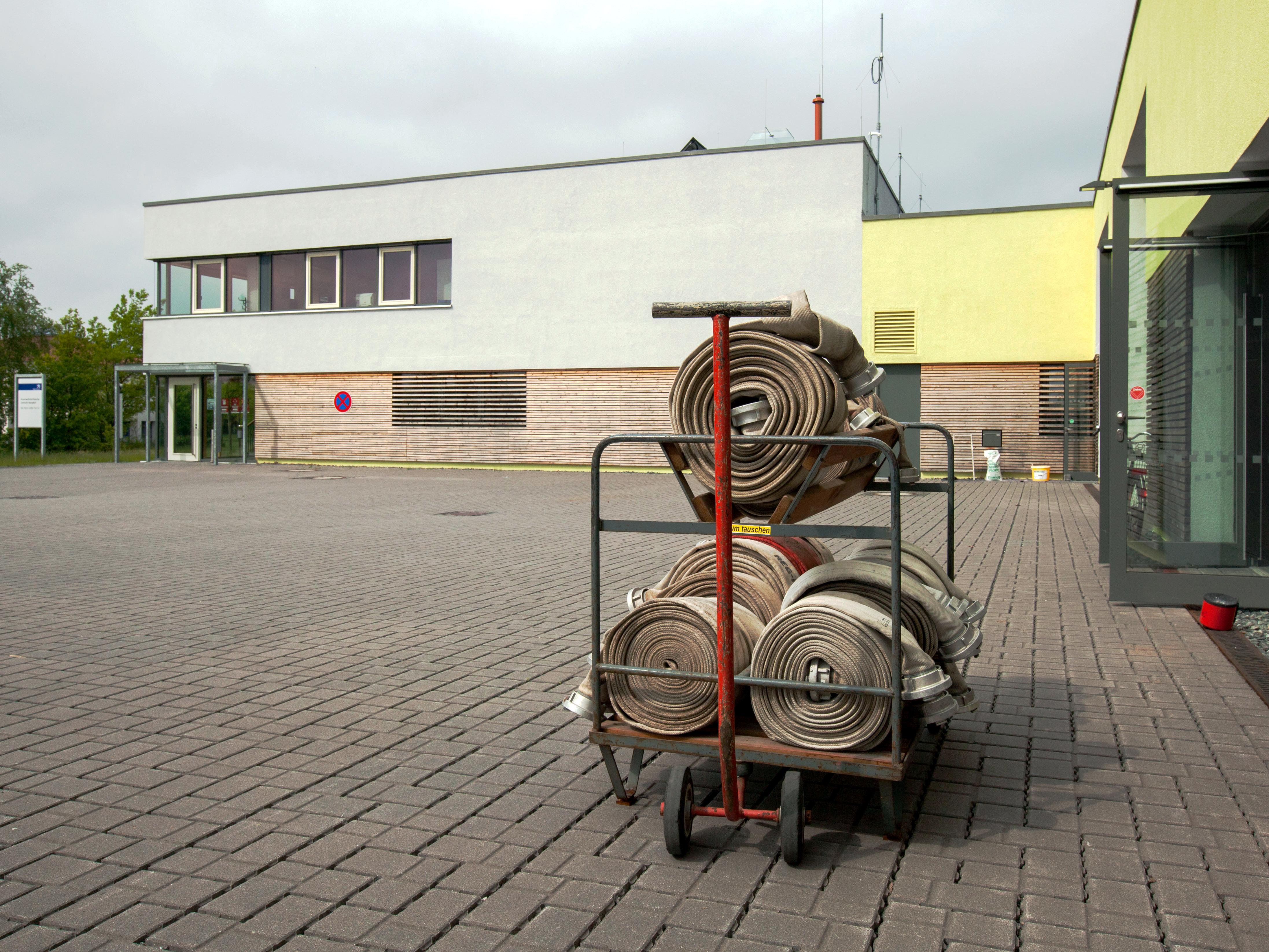 Auf einem Handkarren liegen Feuerwehrschläuche, im Hintergrund ist die Feuerwehrtechnische Zentrale (FTZ) Burgdorf