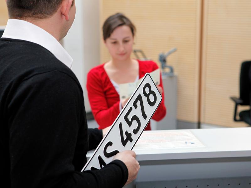 Bürger mit Kfz Kennzeichen am Tresen des Bürgerbüros.