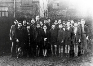 Pupils with a teacher in front of the northern side of the school building in 1940