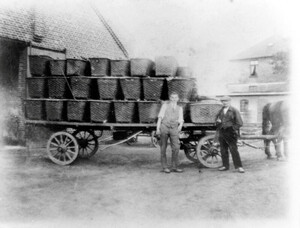 A scene from the first half of the 1920s: two employees with market produce in front of the barn. The assistants' house can be seen on the right.