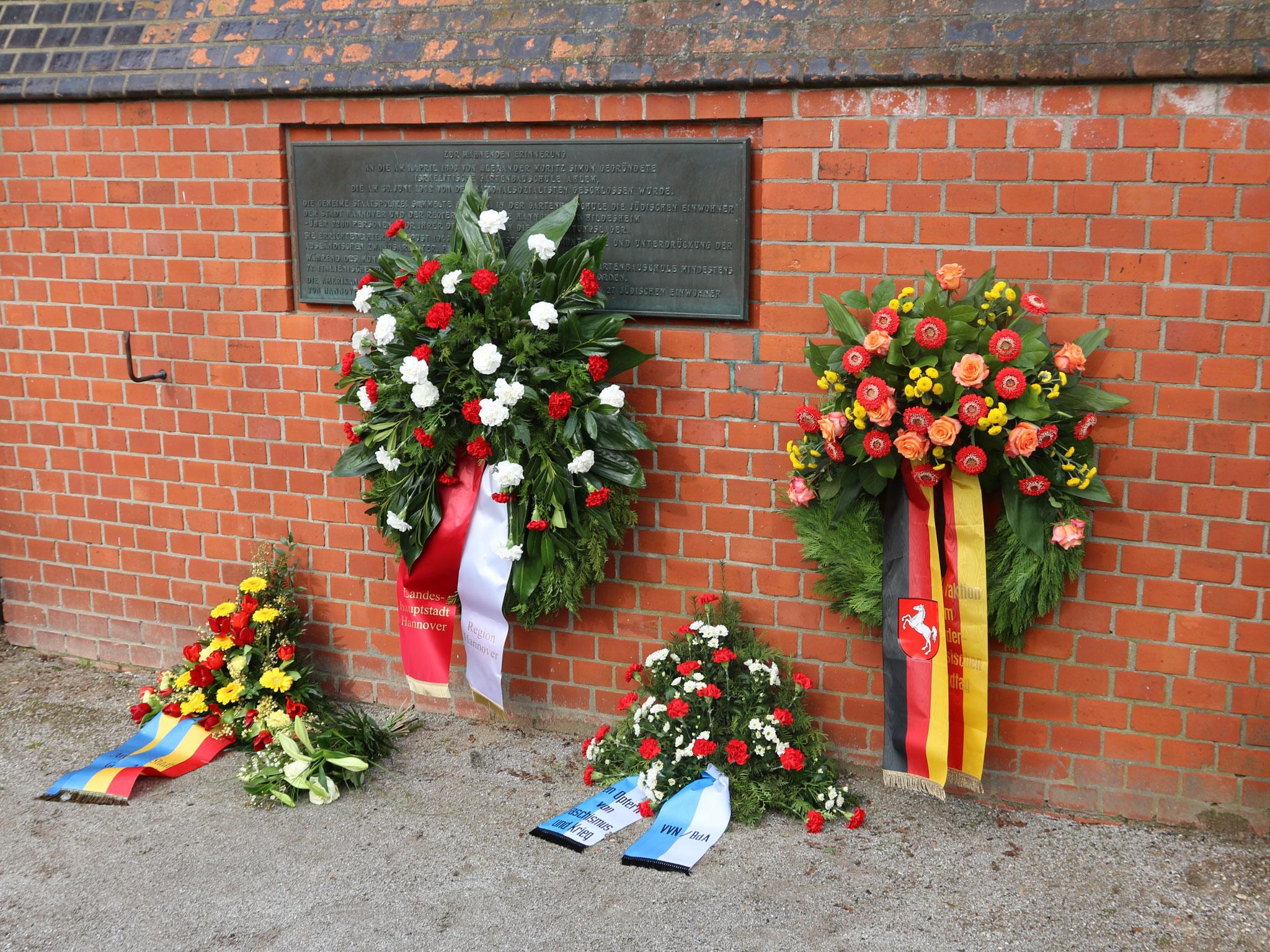 Vier Gedenkränze vor bzw. an einer Mauer.