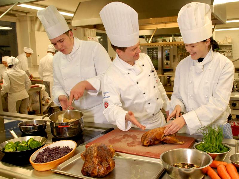 Geflügel, Rotkohl und Brokkoli: zwei Köche und eine Köchin bereiten Speisen zu.