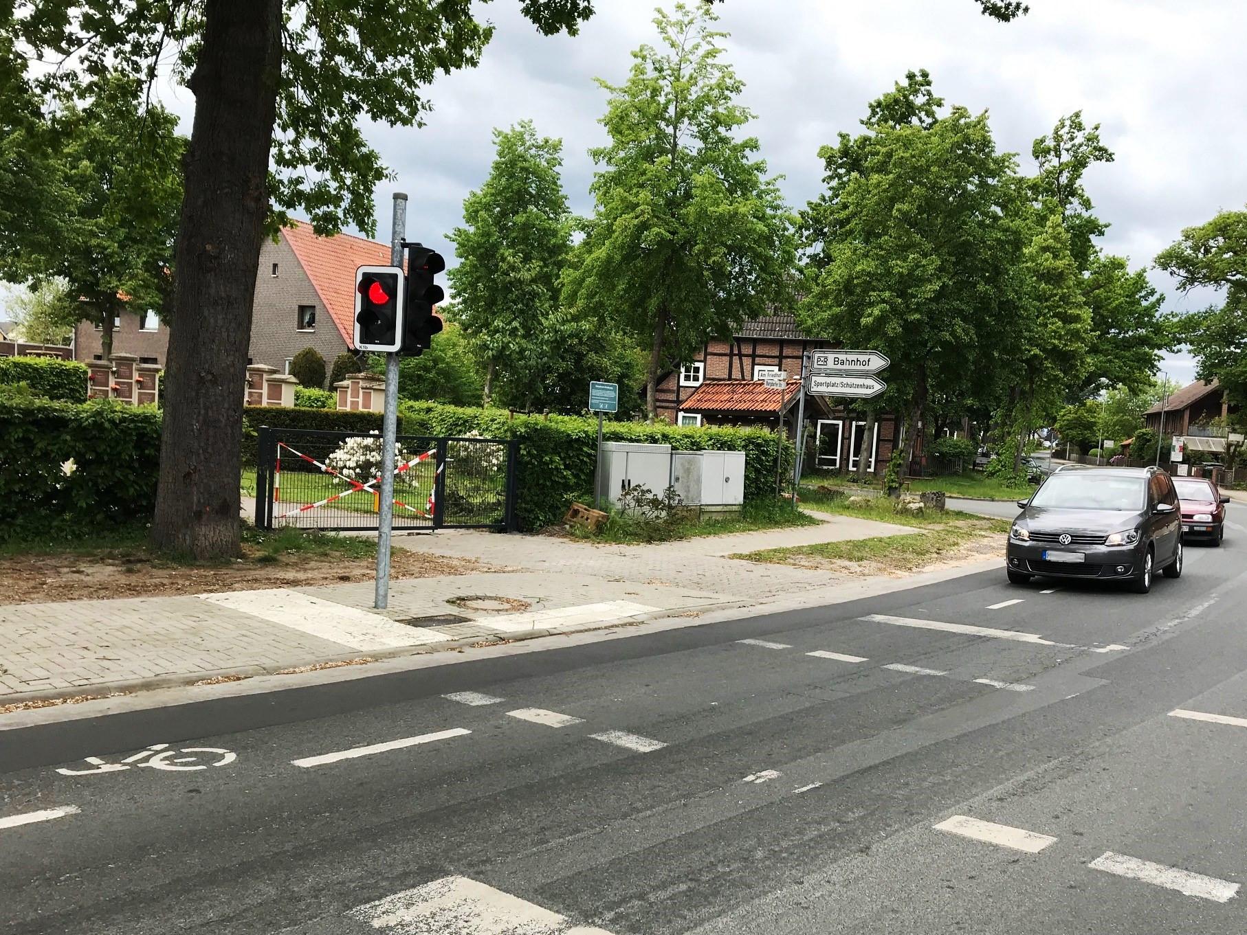 Eine Fußgängerampel zeigt rot, zwei Autos warten davor.