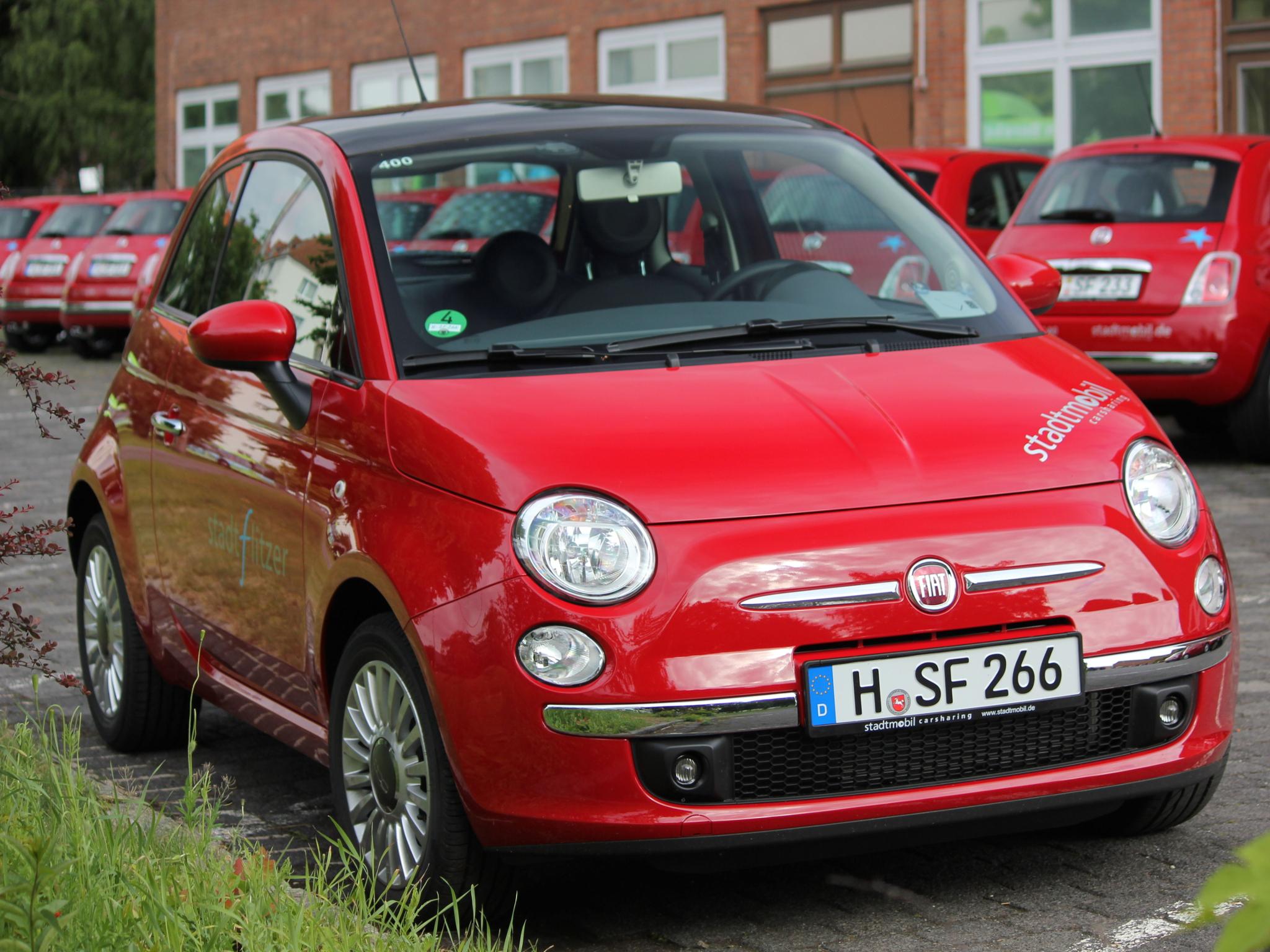 Roter Kleinwagen auf Abstellplatz.