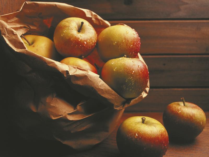 Äpfel in und neben einer Papiertüte
