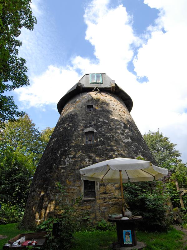 Blick von unten nach oben an der Fassade einer Mühle ohne Windmühlenblätter