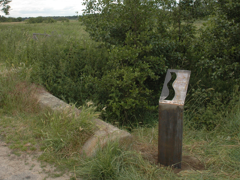 Metalltafel mit Gravur am Wegrand in Bachnähe