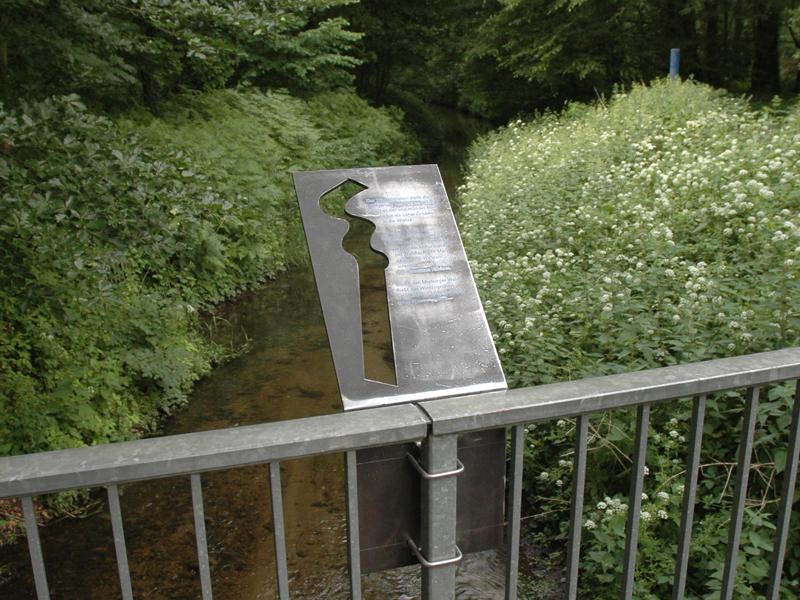 Metalltafel an einem Brückengeländer