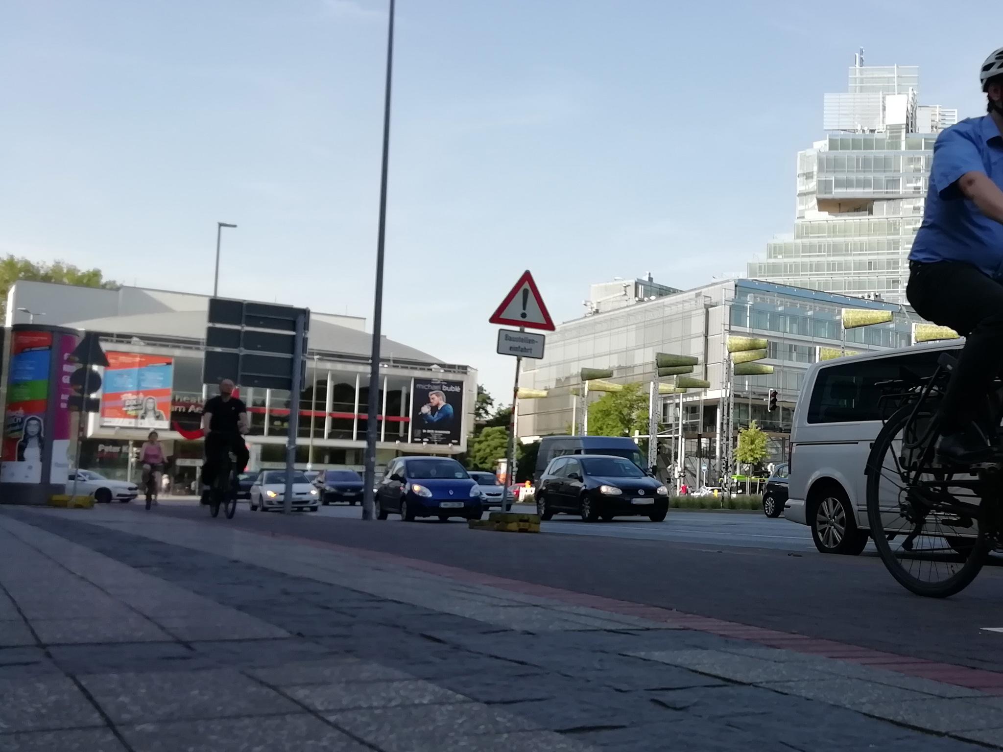 Blick auf einen Platz mit viel Autoverkehr und Fahrrädern daneben auf einem Radweg. Im Hintergrund sind Gebäude zu erkennen.