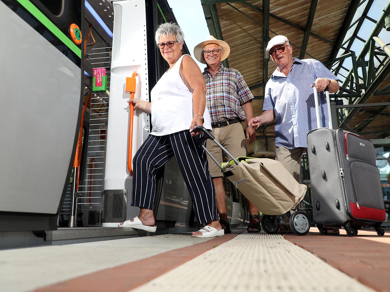 Drei ältere Menschen steigen in eine Stadtbahn ein