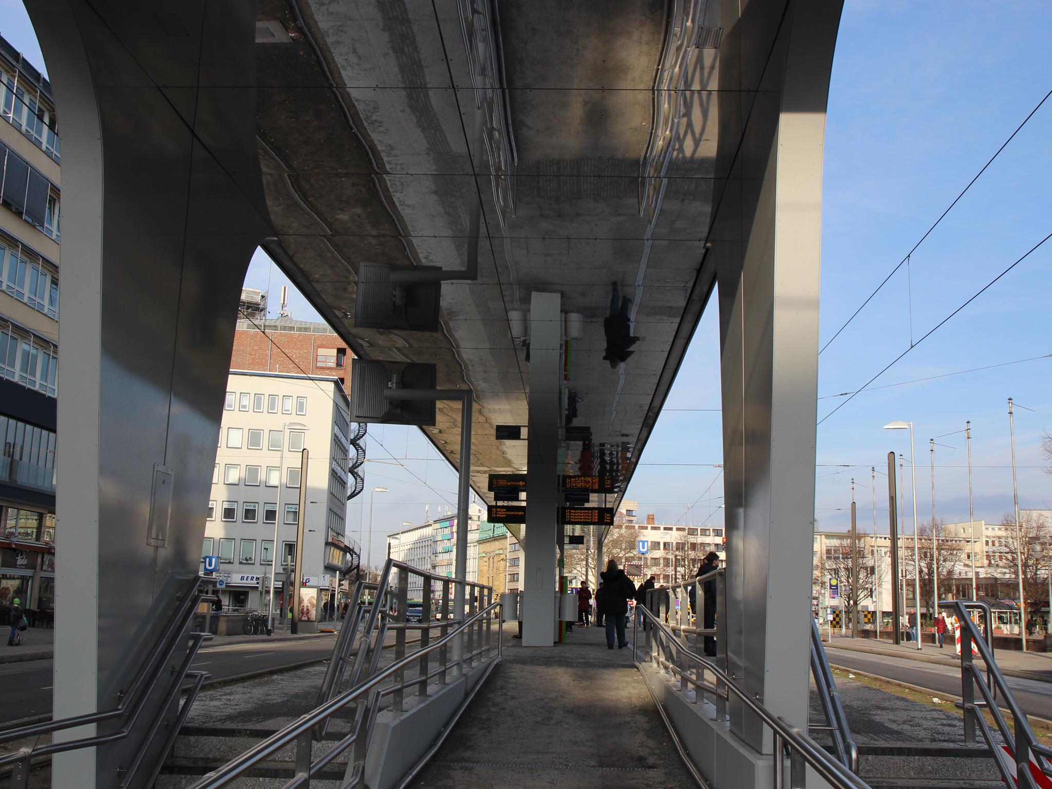 Moderne Haltestelle einer Straßenbahn mit verspiegeltem Dach