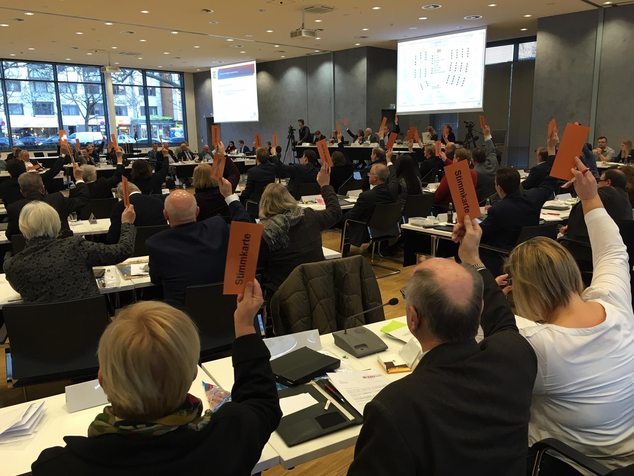 Ein Saal voller Menschen, die an Tischen sitzen. Viele halten eine Stimmkarte in die Höhe.