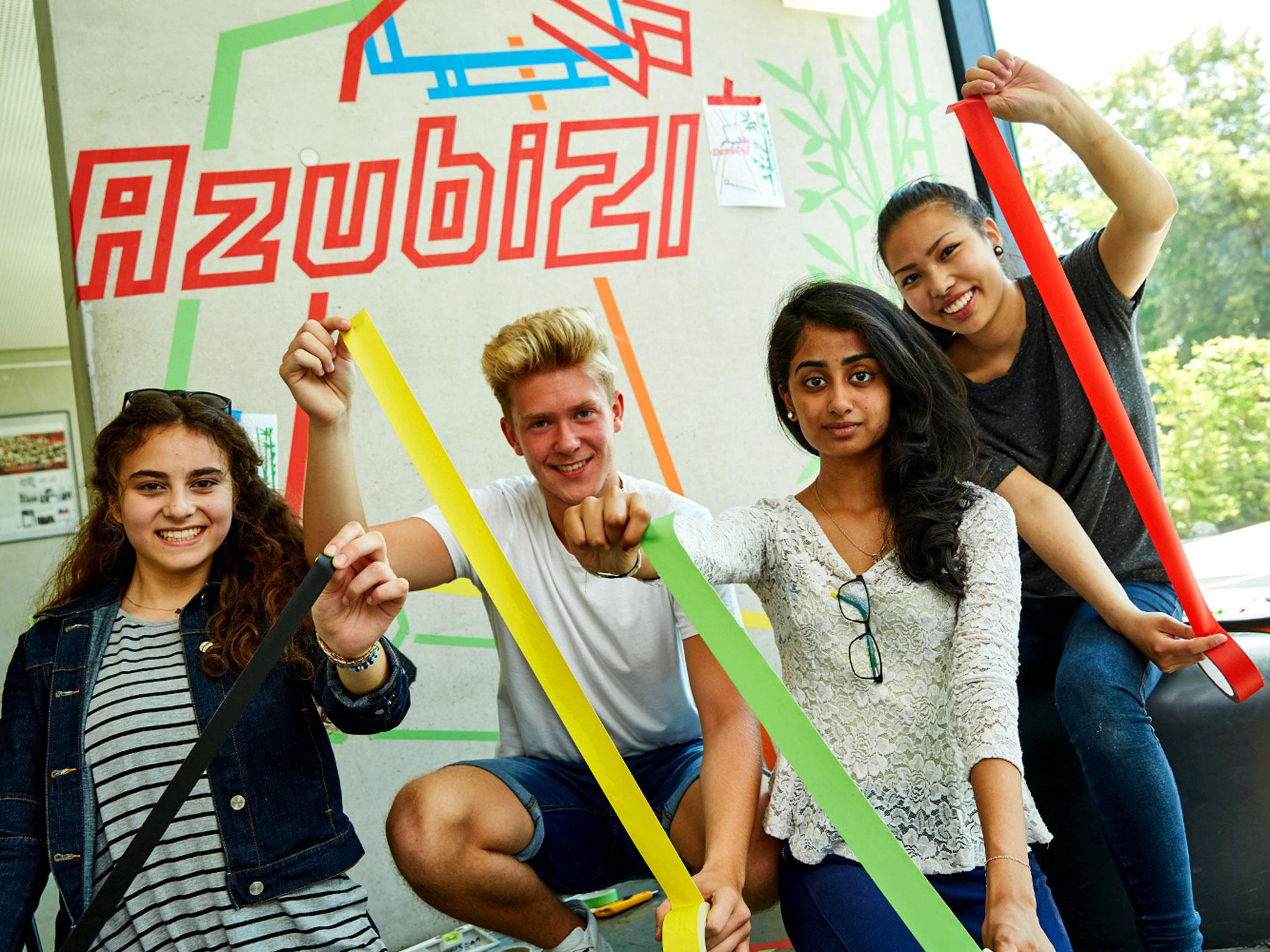 """Drei Junge Frauen und ein junger Mann mit Tape in unterschiedlichen Farben. Hinter ihnen ist """"Azubi21"""" geklebt."""
