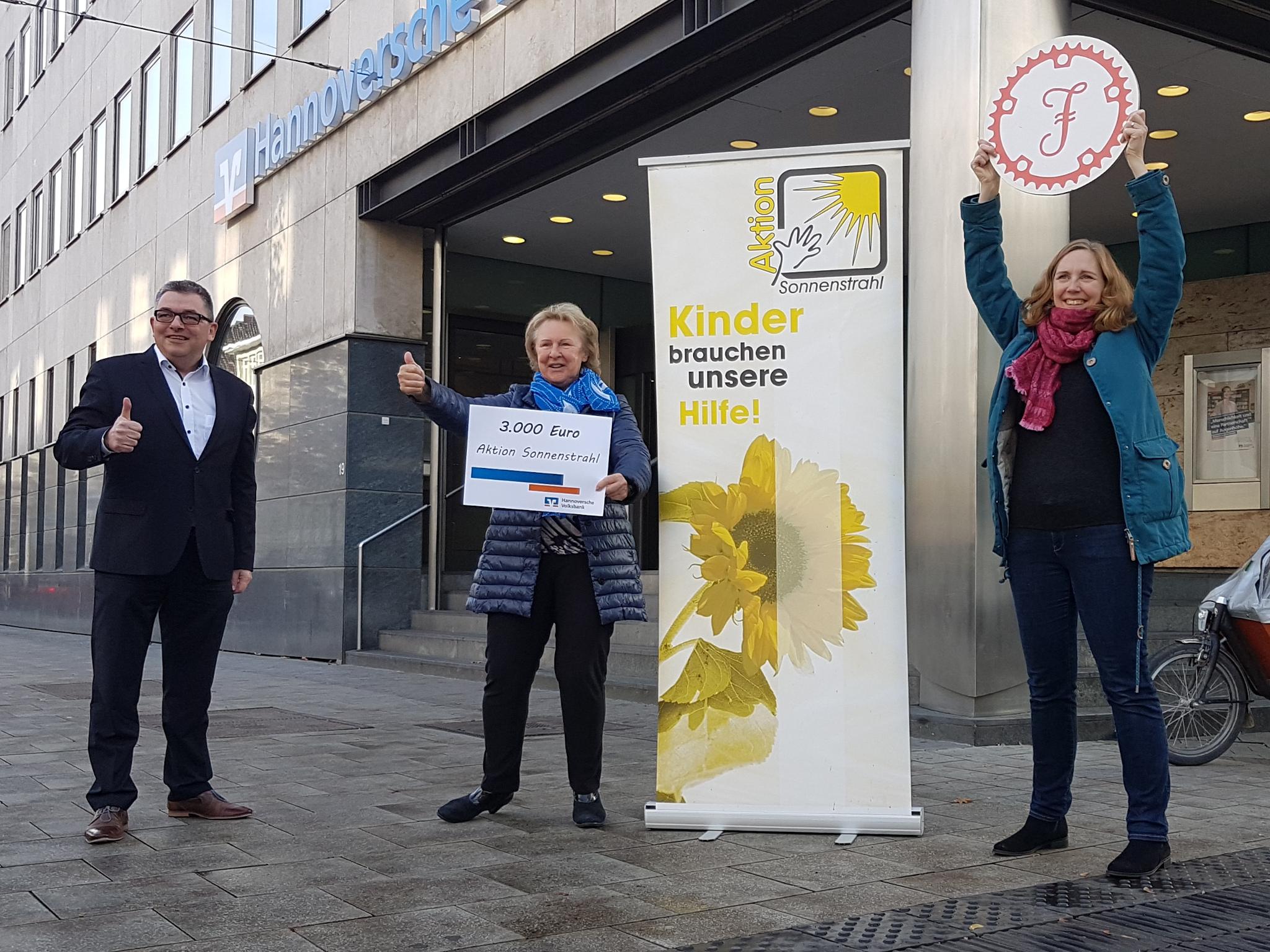Drei Personen vor einem modernen Gebäude, alle freuen sich, zwei halten den Daumen hoch, eine Person hält ein rundes Schild in die Höhe