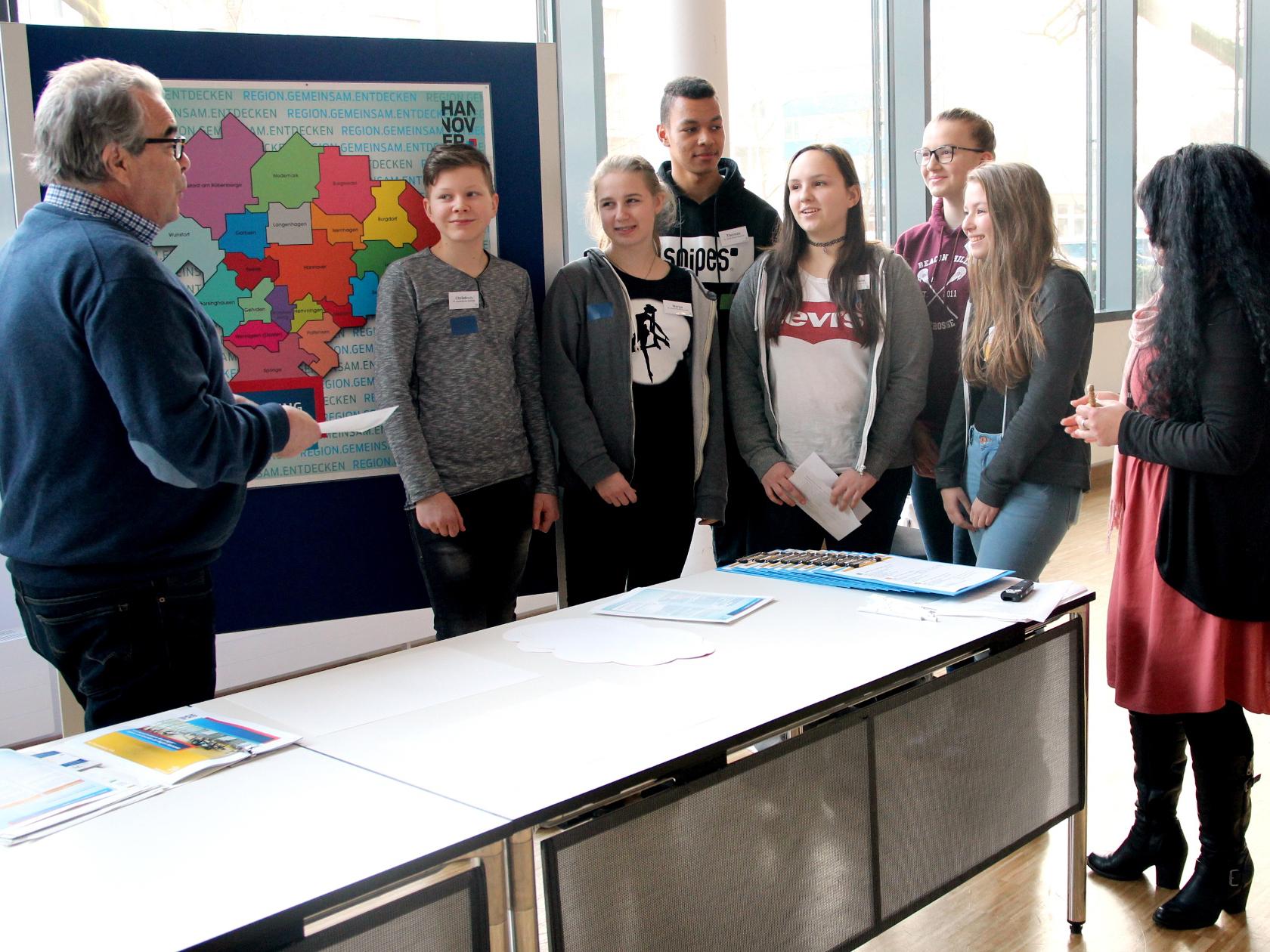 Eine Frau und ein Mann erklären Schülerinnen und Schülern etwas an einer Metaplanwand.