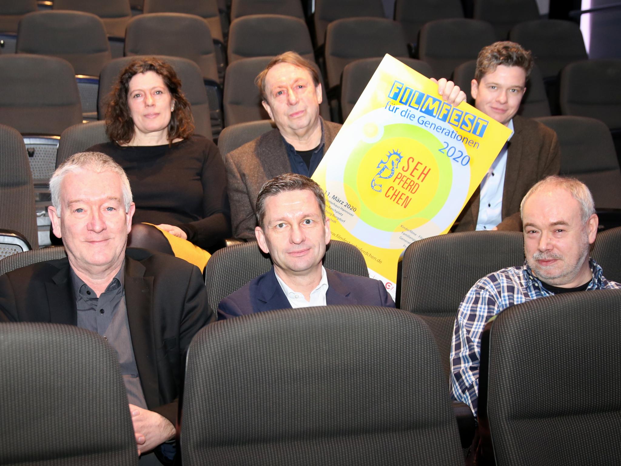 Eine Frau und fünf Männer sitzen in Kinosesseln.