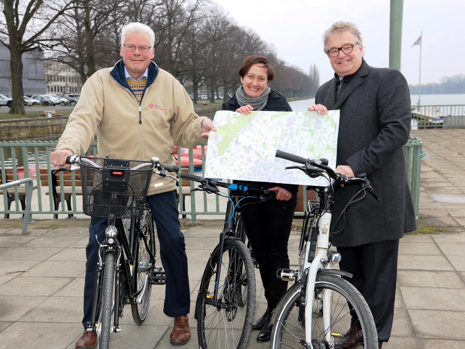 Eine Frau und zwei Männer stehen mit ihren Fahrrädern an einem Ufer und halten eine Radkarte in die Kamera.