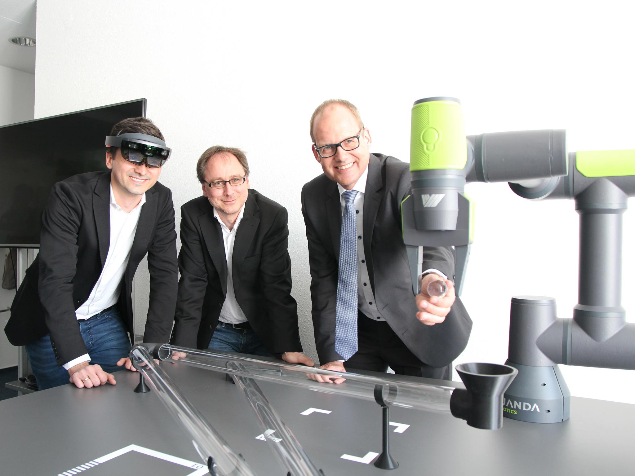 Drei Männer testen einen Roboter.