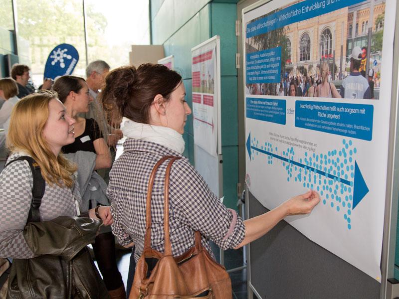 Menschen vor Stellwänden, eine junge Frau klebt einen Markierungspunkt auf ein Plakat