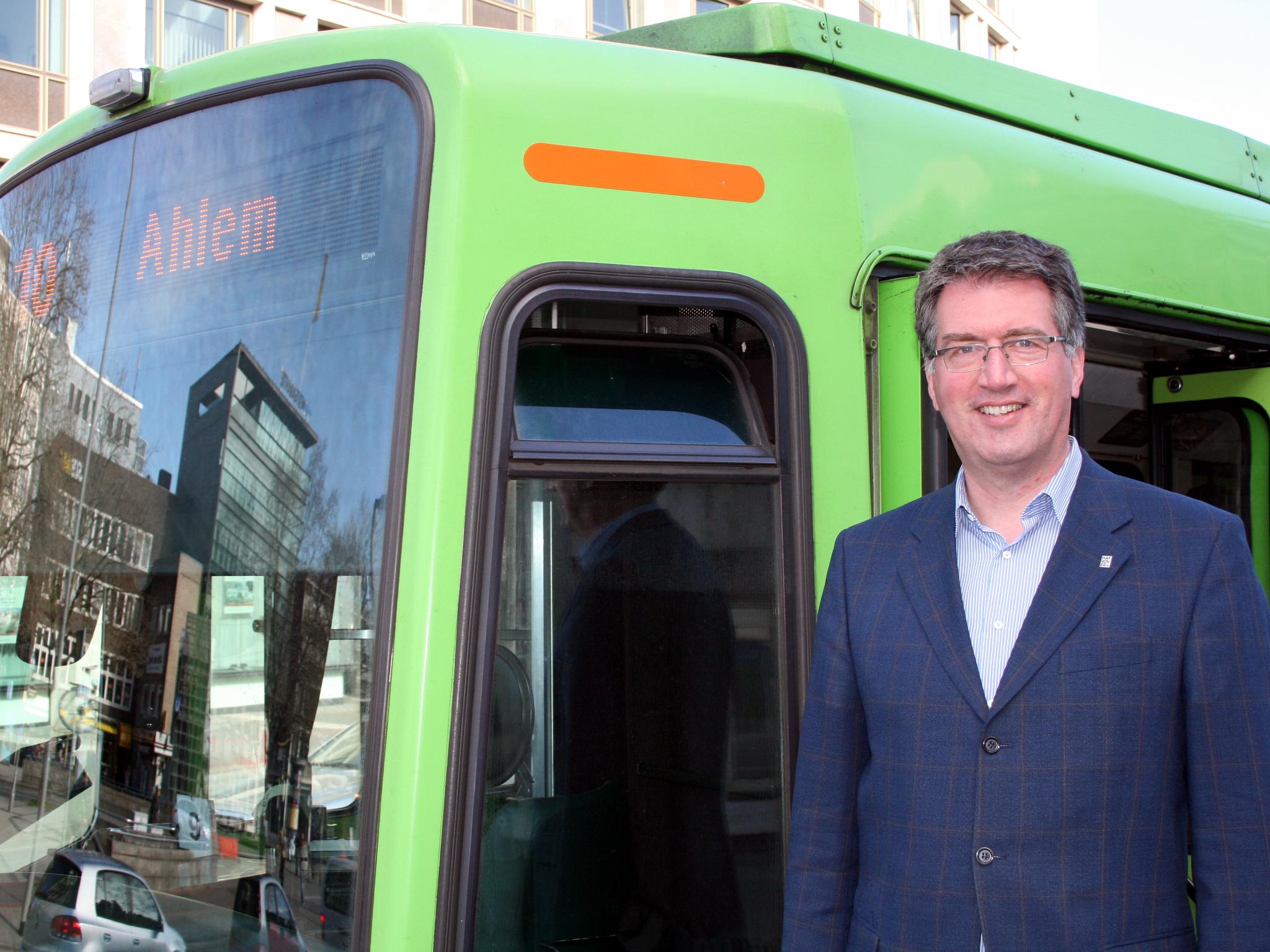 Ein Mann steht an einer Stadtbahn und sieht in die Kamera. Die Tür der Stadtbahn ist geöffnet.
