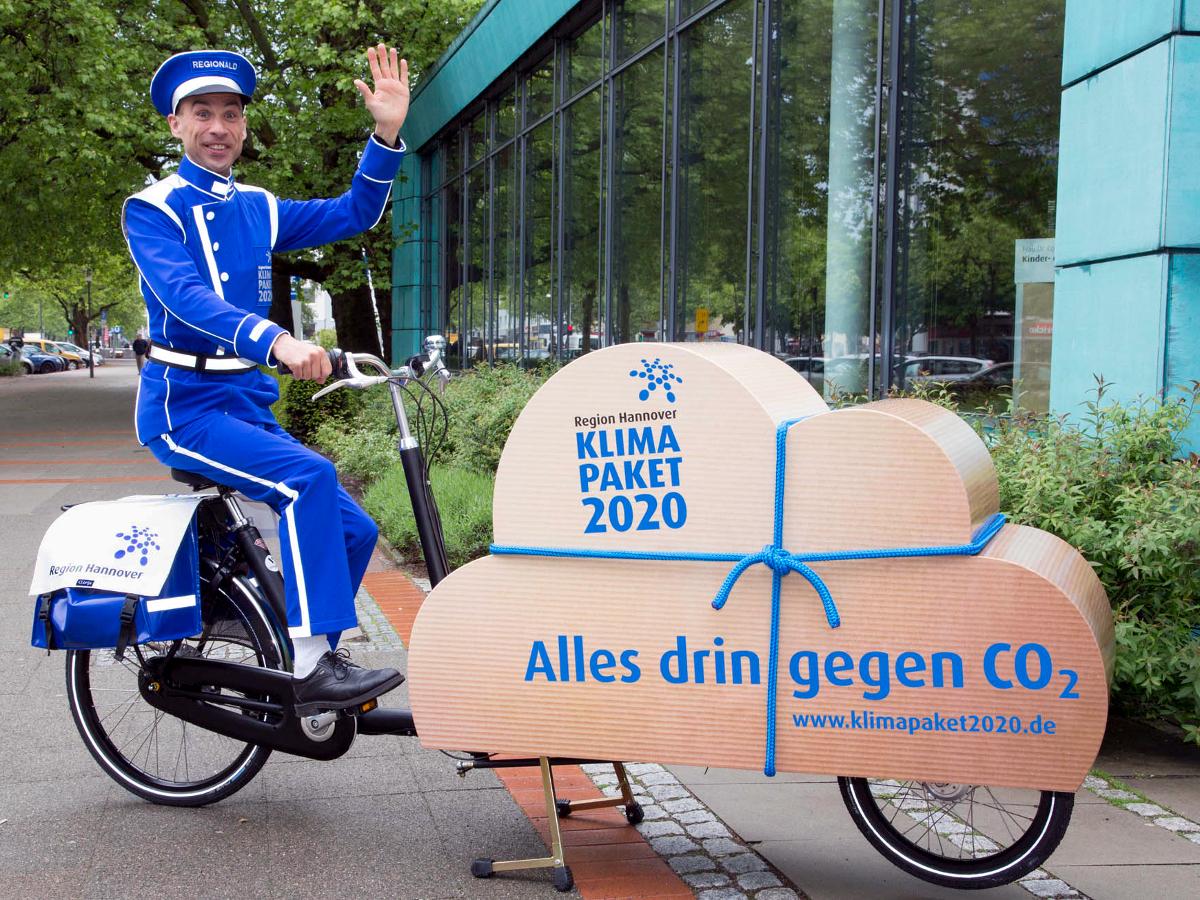 """Ein Mann trägt einen blauen Dienstbotenanzug, auf der Mütze steht """"Regionald"""". Er sitzt auf einem Lastenfahrrad und transportiert ein geschnürtes Paket in Form einer Wolke. Auf dem Wolkenpaket steht """"Region Hannover. Klimapaket 2020. Alles drin gegen CO2. www.klimapaket2020.de"""