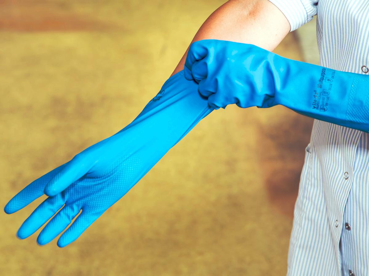 Eine Frau streift sich zwei blaue Putzhandschuhe über die Hände.