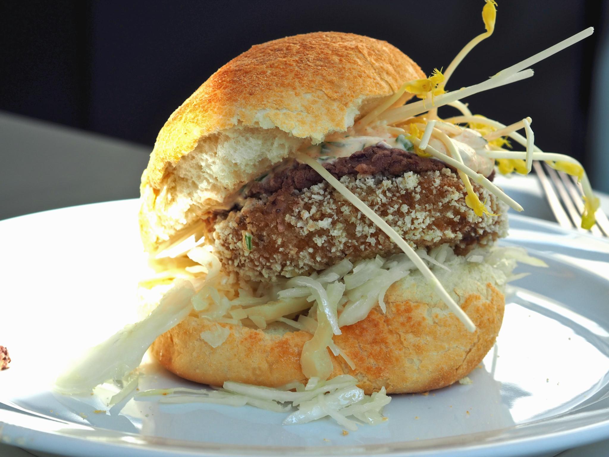 Zwischen zwei hellen, knusprigen Brötchenhälften sind Krautsalat, eine vegetarische Bulette, Rotkrautdip, Knoblauchsoße und Sprossen übereinander gestapelt. Der vegetarische Burger liegt auf einem Teller und wird von links von Sonnenlicht beschienen. Im Hintergrund liegt eine Gabel.