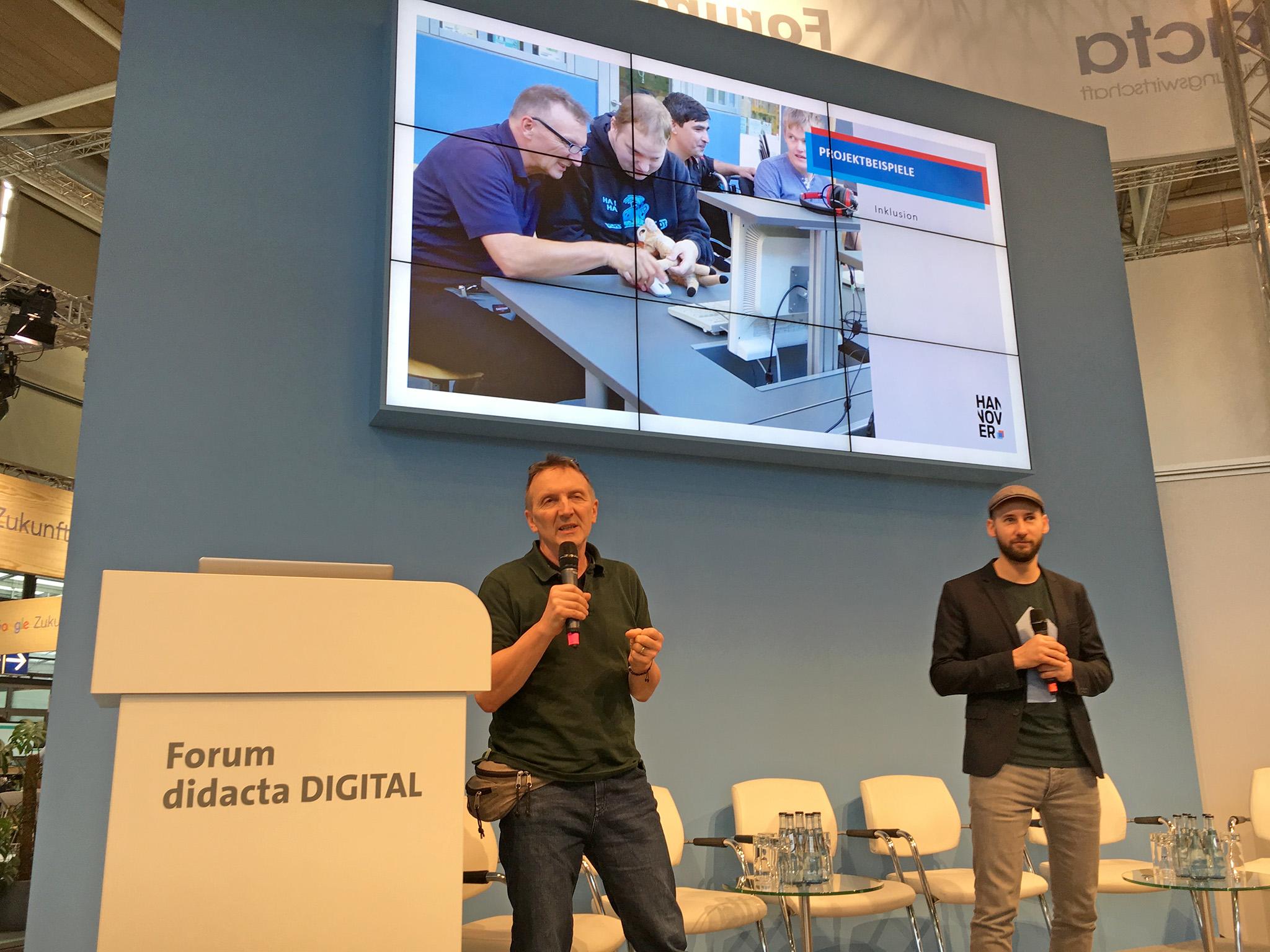 Zwei Männer mit Mikrofonen stehen auf einer Bühne in einer Messehalle. Hinter ihnen läuft auf einem großen Bildschirm eine PowerPoint Präsentation zum Thema Digitale Inklusion - wie Menschen mit Einschränkungen neue Medien nutzen.