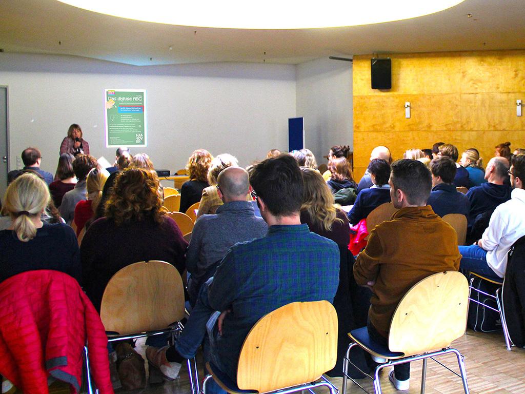 Der große Saal im Freizeitheim Vahrenwald ist mit 60 Teilnehmenden besetzt, Frau Claudia Schulze steht vorn und moderiert die Veranstaltung.