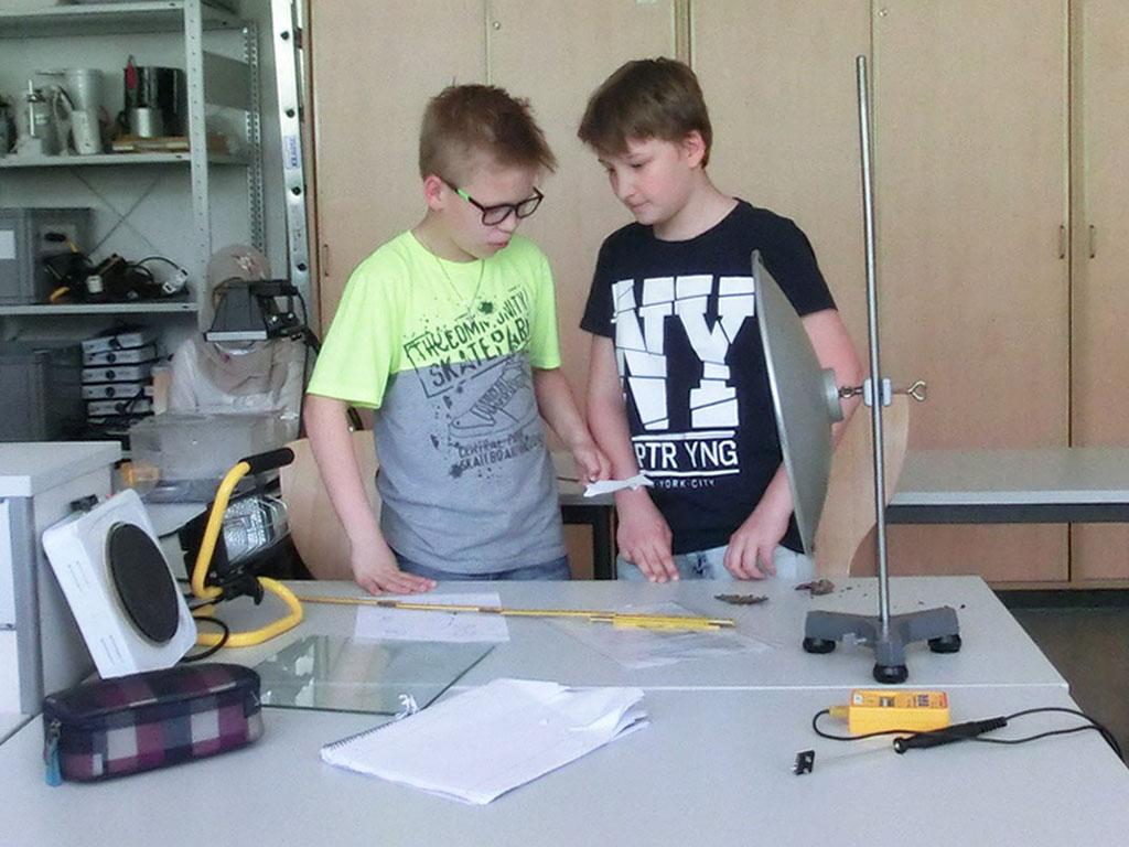 Zwei Schüler an einem Untersuchungstisch führen ein Experiment mit elektromagnetischer Strahlung durch