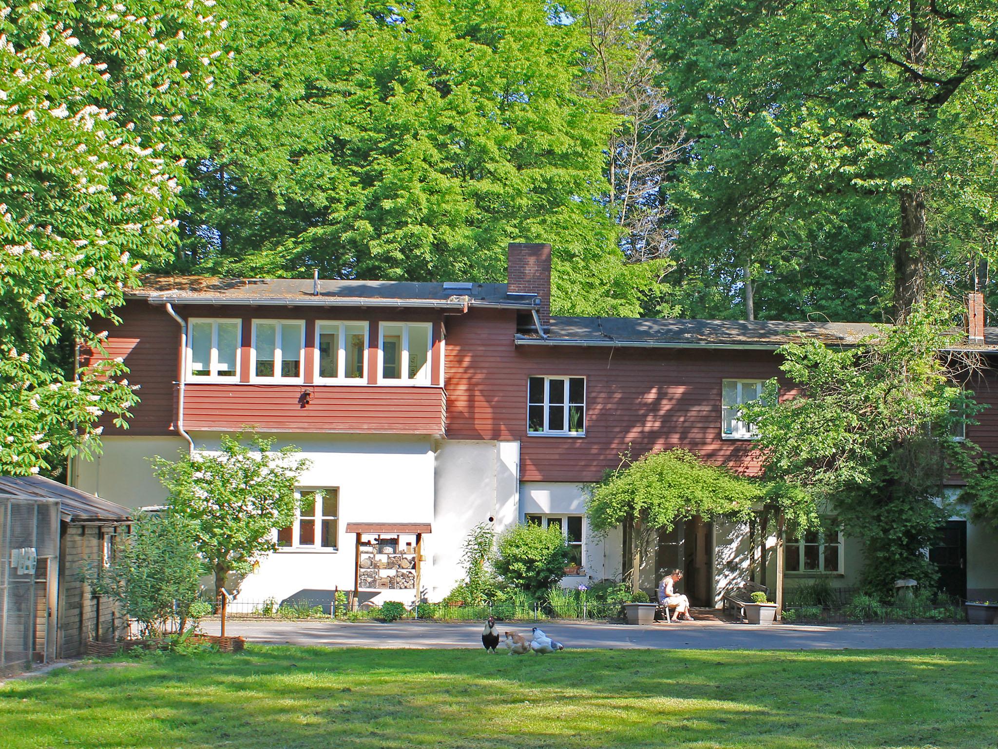 Vor einem zweistöckigen Gebäude umrandet von alten Bäumen sitzt eine Frau vor der geöffneten Tür. Auf dem Rasen davor picken drei Hühner, links im Bild steht ein Insektenhotel.